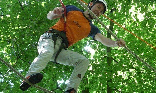 Mann klettert im Hochseilgarten